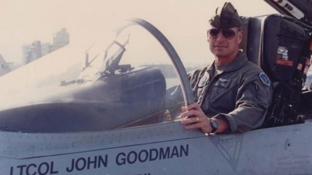 A pilot poses for a photo in the cockpit of an aircraft.