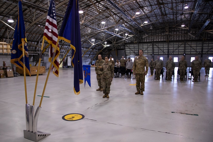 Soldiers from the 2nd Battalion, 641st Aviation Regiment stand for the National Anthem during a casing ceremony at the unit's aircraft hangar on Joint Base Elmendorf-Richardson, July 9, 2021. The traditional casing ceremony was held as the unit prepares to leave for the mobilization station at Fort Bliss, Texas, prior to deployment overseas. (U.S. Army National Guard photo by Victoria Granado)