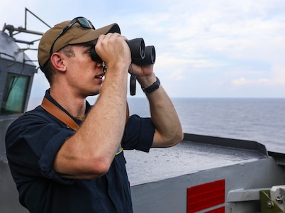 SOUTH CHINA SEA (July 12, 2021) Lt.j.g. Andrew Hayne, from Parker, Colo., uses binoculars to monitor a surface contact from the bridge wing of the Arleigh Burke-class guided-missile destroyer USS Benfold (DDG 65) while conducting routine underway operations. Benfold is forward-deployed to the U.S. 7th Fleet
