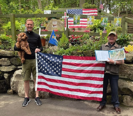 """Tony Foulds, right, and Dan Walker pose for a photo with a U.S. flag July 11, 2021, in front of a memorial honoring the U.S. Army Air Forces crew of a B-17 Flying Fortress, """"Mi Amigo,"""" who lost their lives when their aircraft crashed in February 1944 in Sheffield, England. The memorial was vandalized in March 2021 then again in July, and many items including flags were destroyed. Leadership from Royal Air Force Mildenhall sent the flag on behalf of the 100th Air Refueling Wing – which was flown on board a KC-135 Stratotanker aircraft mission over Normandy, France, on the anniversary of D-Day – to place at the memorial in honor of the Mi Amigo crew. Tony has dedicated his life to preserving the memorial built to remember the crew who lost their lives. Walker is a television presenter who met Tony while walking his dog, learned of his story and worked to arrange a flyover in Sheffield to mark the 75th anniversary of the crash in February 2019. (Courtesy photo)"""