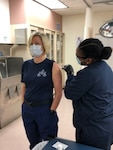 Chief Petty Officer Maureen Potratz, a member of the Coast Guard Base Rockmore-King Clinic staff, receives a COVID-19 vaccination shot by Petty Officer 2nd Class Qarina Orlowski, in Kodiak, Alaska, on Jan. 8, 2021. Coast Guard 17th District personnel are working diligently to vaccinate servicemembers to combat the spread of COVID-19. U.S. Coast Guard photo by Capt. Charles Truncale.