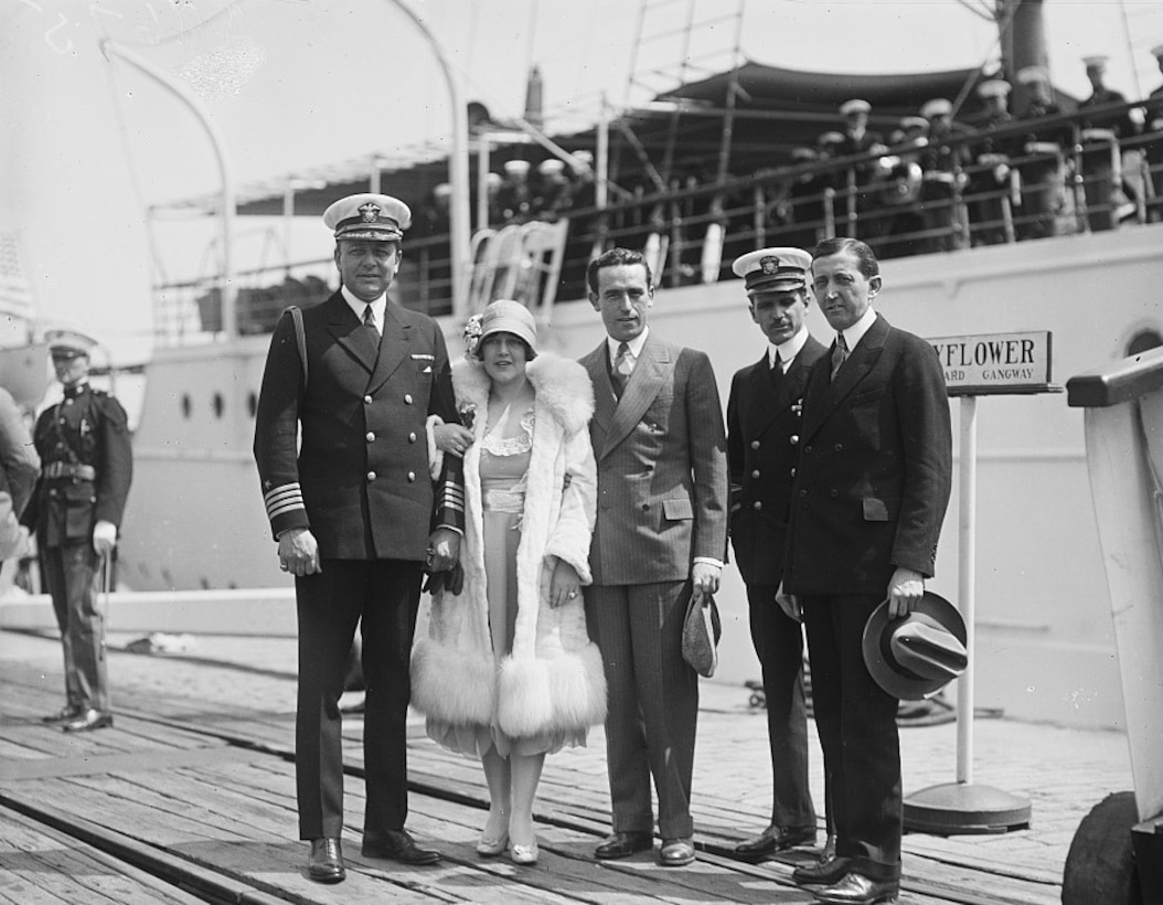 Five people in 1920s-style garb pose for a photo on the dock beside a yacht filled with sailors.