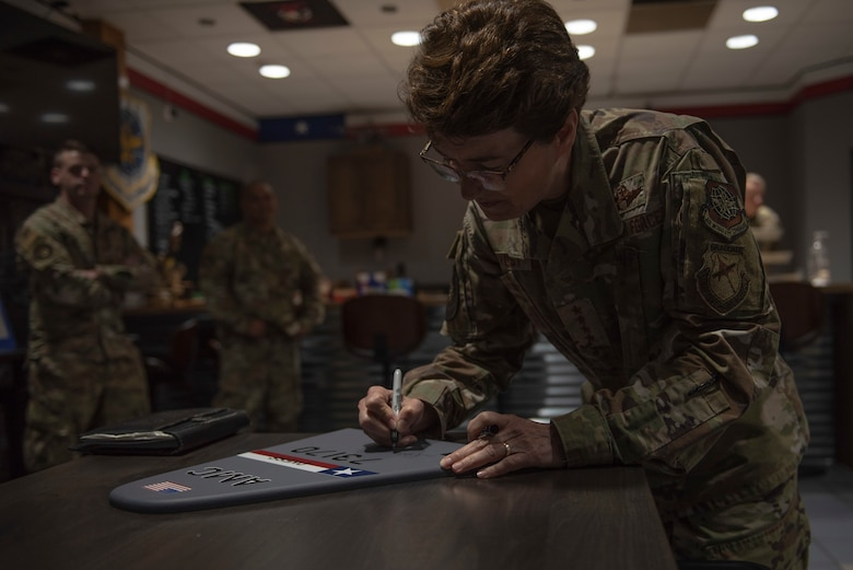 U.S. Air Force Gen. Jacqueline Van Ovost, Air Mobility Command commander, signs a C-130J Super Hercules tail flash at Dyess Air Force Base, Texas, July 8, 2021. The 317th Airlift Wing traditionally has distinguished visitors sign a tail flash to commemorate their visit. (U.S. Air Force photo by Senior Airman Colin Hollowell)
