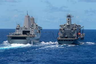 Amphibious transport dock USS New Orleans (LPD 18) (left) recieves fuel lines from USNS Tippecanoe (T-AO 199).