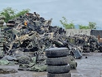 tires stacked in front of a scrap pile