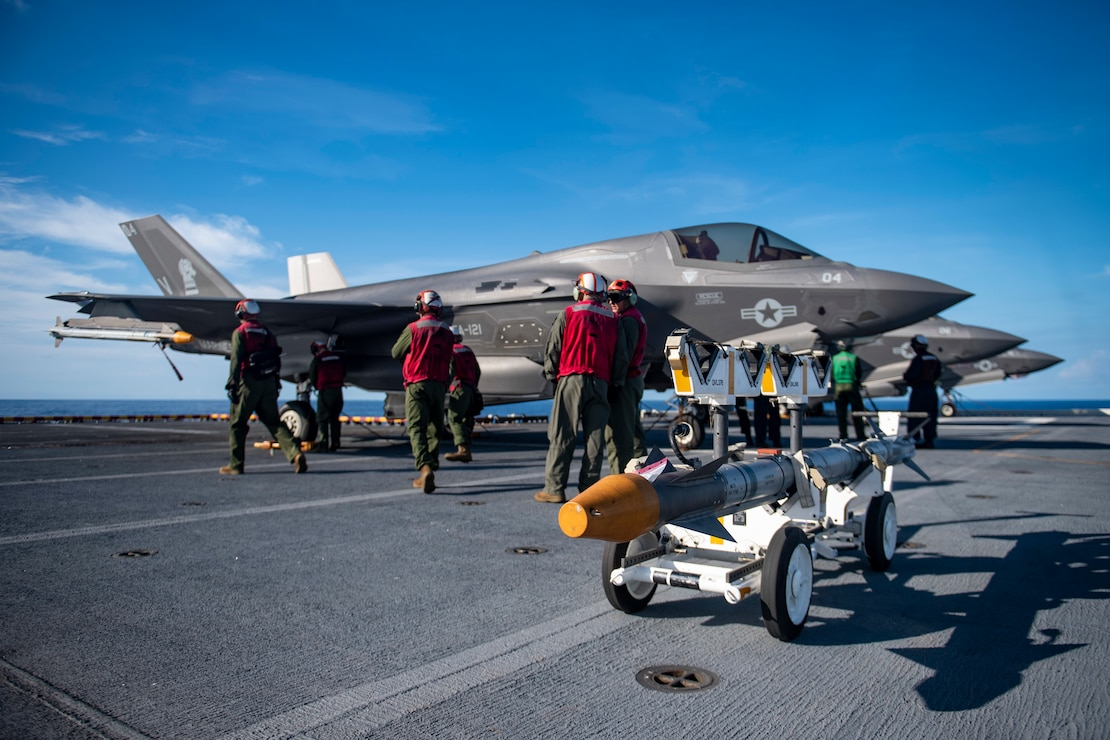Marines assigned to the 31st Marine Expeditionary Unit (MEU) prepare to download inert ordnance from an F-35B Lightning II fighter aircraft on the flight deck of the forward-deployed amphibious assault ship USS America (LHA 6).