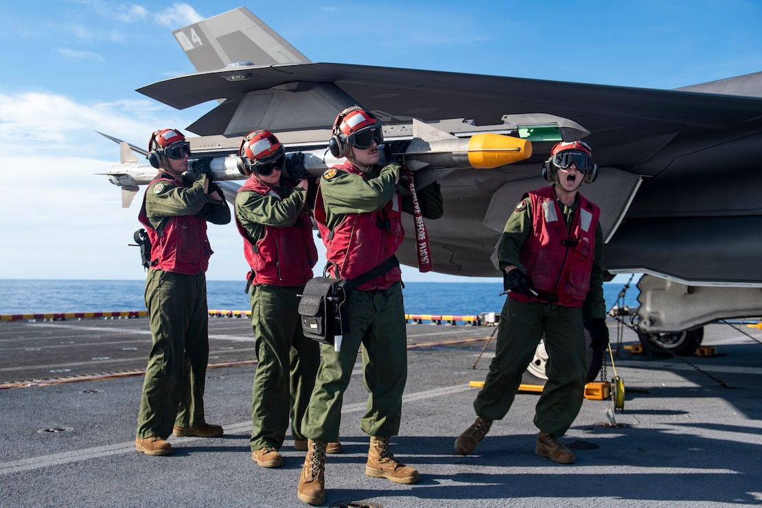 Marines assigned to the 31st Marine Expeditionary Unit (MEU) download inert ordnance from an F-35B Lightning II fighter aircraft on the flight deck of the forward-deployed amphibious assault ship USS America (LHA 6).