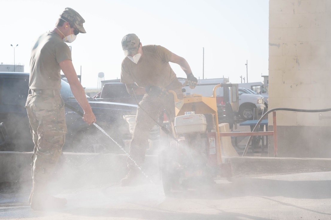 Senior Airman Garrett Cothran, left, and Airman 1st Class Christian Atkins, right, 341st Civil Engineer Squadron heavy equipment operators, make relief cuts into new concrete July 14, 2021, at Malmstrom Air Force Base, Mont.