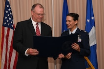 Richard Aldridge, program executive officer for Business and Enterprise Systems and director of the Business and Enterprise Systems Directorate at Maxwell Air Force Base, Ala., presents Col. Martha Monroe with a certificate during a retirement ceremony at Hanscom Air Force Base, Mass., July 9.