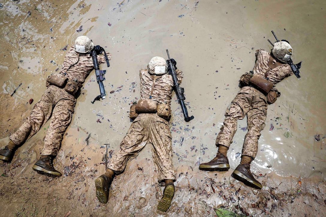 Three Marine Corps recruits lie in mud.