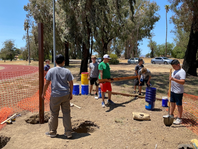 Boy scouts and Airmen work together to install pull-up bars on a dirt patch.