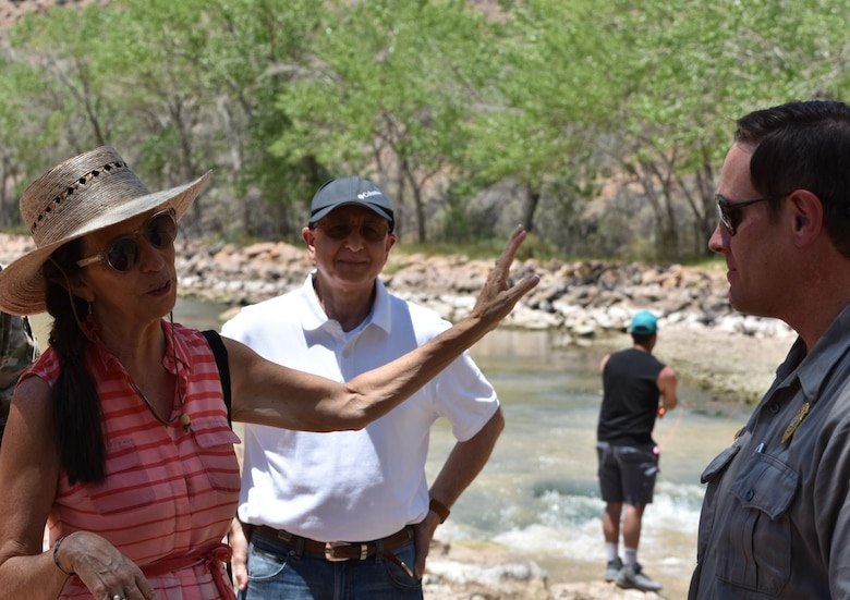 Congresswoman Teresa Leger Fernández (left) discusses the Rio Chama Habitat Improvement project with Nabil Shafike, chief water management (center) and John Mueller, lake operations manager, Abiquiu Lake, during her visit to Abiquiu Lake and Dam, July 10, 2021. In the background a fisherman practices his fly-fishing.
