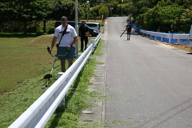 気温35度近くの炎天下の下、ボランティアで草刈り作業に励む隊員ら、沖縄県金武町中川地区公民館近く、2021年7月14日