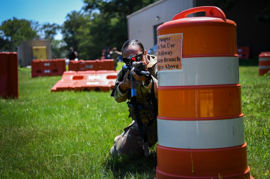 Senior Airman Adrianna Williams, 66th Security Forces Squadron entry controller, shoots from behind a blockade while wearing female body armor during a tactical exercise at Hanscom Air Force Base, Mass., June 29.  The newest development in Air Force body armor is designed to better protect female Airmen during combat and contingency operations. (U.S. Air Force photo by Lauren Russell)