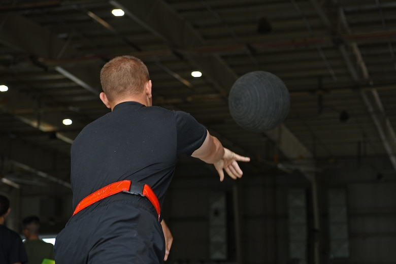 U.S. Army Firefighter Detachment student assigned to the 169th Engineer Battalion, throws a medicine ball for an evaluation, on Goodfellow Air Force Base, Texas, June 30, 2021. Firefighter students were assessed before they started their course by a physical therapist to fix lifting mechanics or strength deficits to prevent injury. (U.S. Air Force photo by Senior Airman Abbey Rieves)