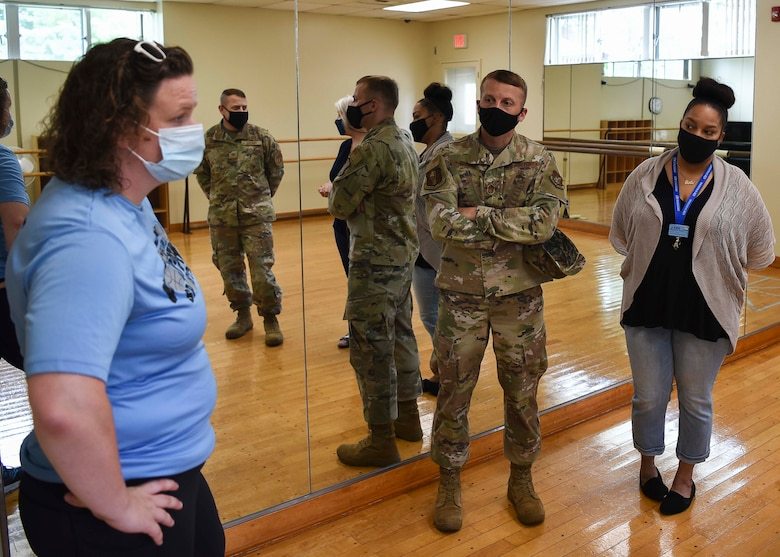 Military members talk to Lunney Youth Center staff members in a dance room.