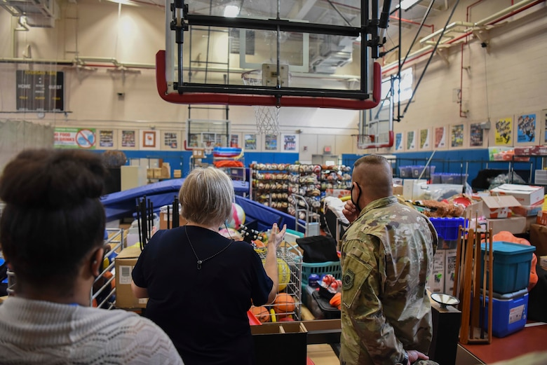 A military member and a Lunney Youth Center staff member look at the equipment the center has in a gym.