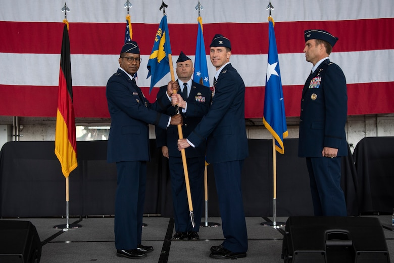 U.S. Air Force Col. David Epperson, 52nd Fighter Wing outgoing commander (center), passes the 52nd FW guidon to U.S. Air Force Maj. Gen. Randall Reed, Third Air Force commander (left), as he relinquishes command during the 52nd Fighter Wing Change of Command ceremony July 15, 2021, on Spangdahlem Air Base, Germany. The 52nd FW commander oversees all five of the wing's groups, who directly support the mission to provide strategic, theater and contract commercial air mobility capability for Europe, Africa and Southwest Asia. (U.S. Air Force photo by Staff Sgt. Melody W. Howley)