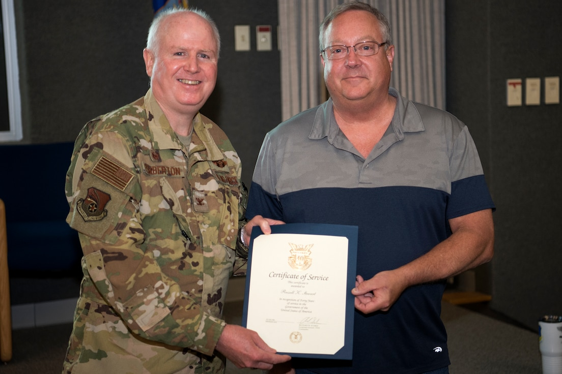 Col. Thom Pemberton, 434th Air Refueling Wing commander, left, presents Rusty Stewart, 434th Maintenance Squadron, a certificate recognizing his 40 years of federal service July 8, 2021. Employees were recognized during a civilian commander's call for 40, 30, 20, and 10 years of service. (U.S. Air Force photo by Douglas Hays)