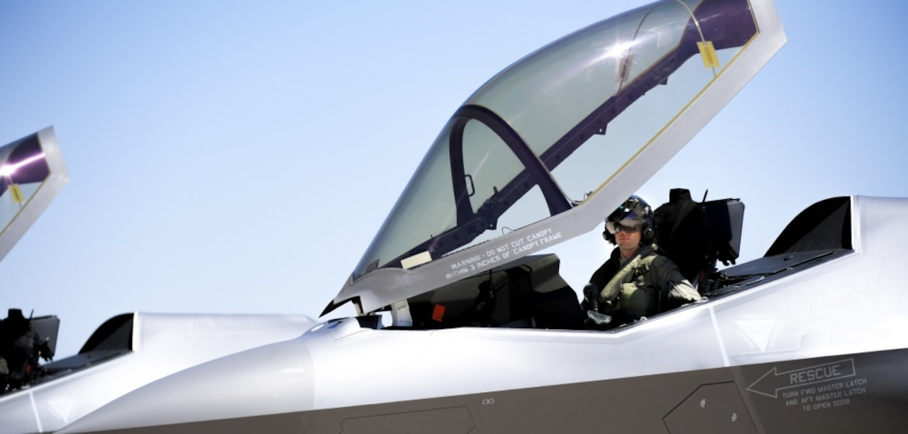 A pilot sits in the cockpit of a jet.