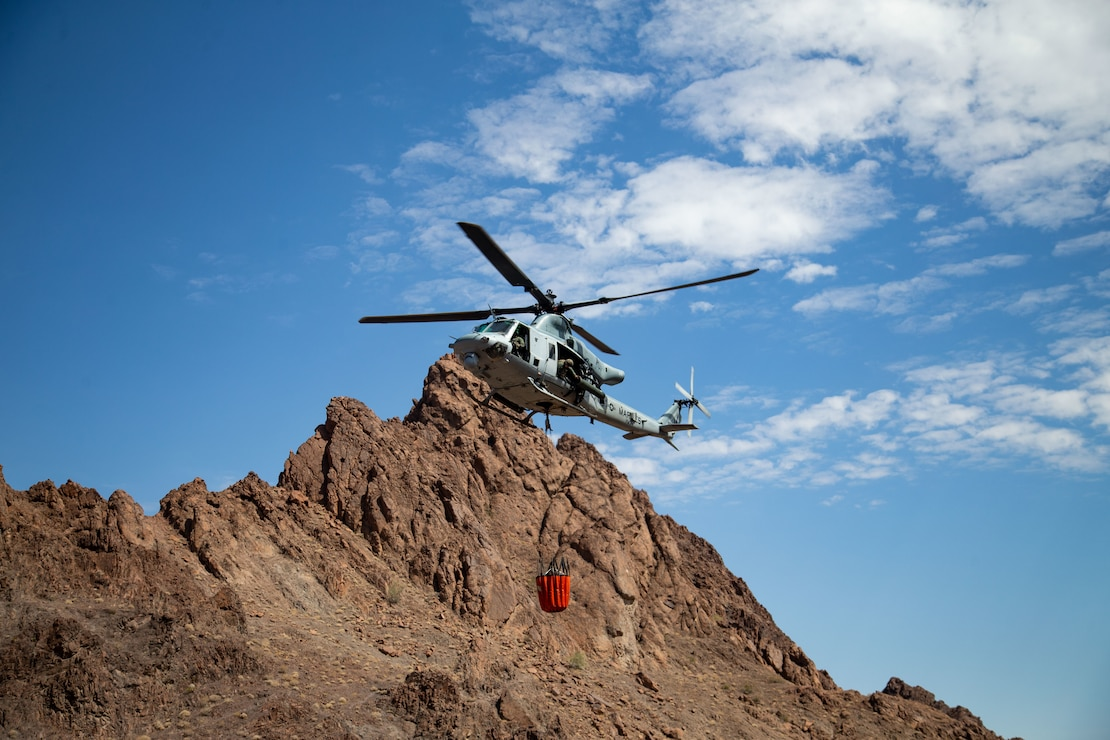 A U.S. Marine Corps UH-1Y Venom with Marine Operational Test and Evaluation Squadron (VMX) 1, dumps water into a watering hole near the Chocolate Mountain Aerial Gunnery Range, Calif., July 7, 2021. Man-made watering holes help animals in the desert access water easily all year round. (U.S. Marine Corps photo by Lance Cpl Gabrielle Sanders)