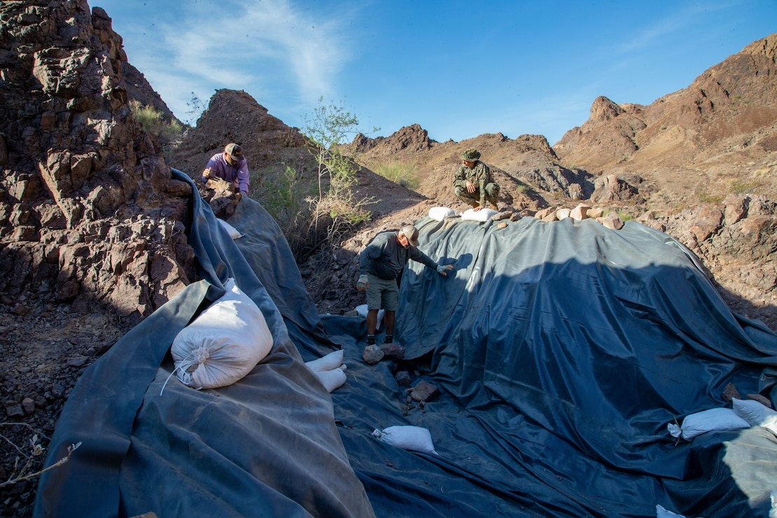 U.S. Marine Corps Sergeant Austin Hall, an aviation radar technician with Marine Operational Test and Evaluation Squadron (VMX) 1, lays tarp down in preparation for the watering hole to collect water near the Chocolate Mountain Aerial Gunnery Range, Calif., July 7, 2021. Man-made watering holes help animals in the desert access water easily all year round. (U.S. Marine Corps photo by Lance Cpl Gabrielle Sanders)