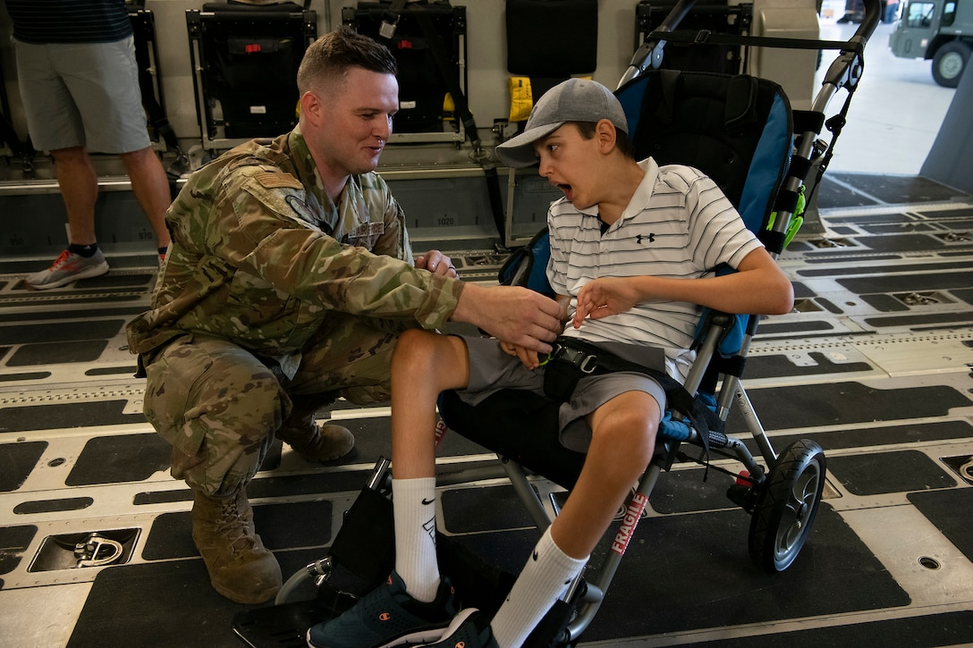 Tech Sgt. Wade Griffith, 437th Maintenance Squadron, gives a unit coin to Braiden Adkins while touring a C-17 Globemaster III at Joint Base Charleston, South Carolina July 14, 2021.