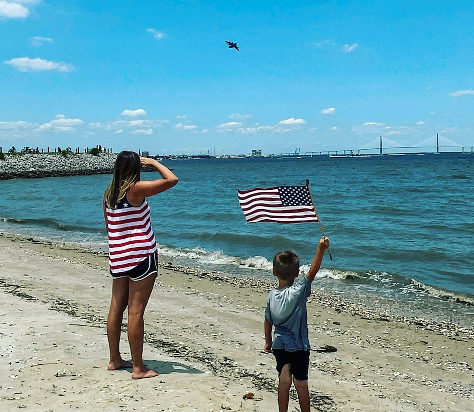 """Airplane fan, Jace Adkins and his mother Leslie enjoy the annual """"Salute from the Shore"""" celebration in Charleston, South Carolina as a C-17 Globmaster III, flown by the 701st Airlift Squadron,  and other aircraft fly over the South Carolin Coast July 4, 2021.  (Photo courtesy Adkins family)"""