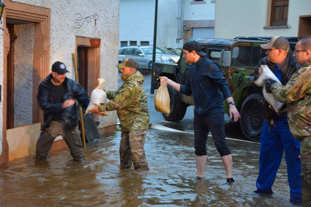 A line of people stand in flood waters handing sandbags to each other.
