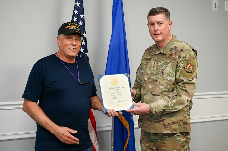 Joseph Friedli and Lt. Gen. Kirland pose for a photo while holding the 50-year certificate in between them.