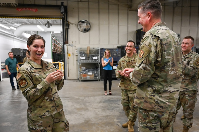 Airman 1st Class Braud stands in surprise in front of a smiling Lt. Gen. Kirkland and other Airmen in the background.