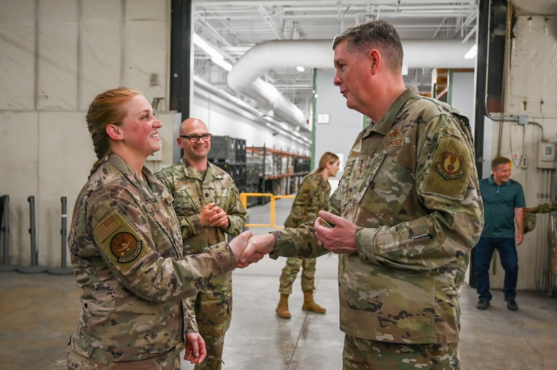 Capt. Shelton shakes hands with Lt. Gen. Kirland while other Airmen look on in the background.