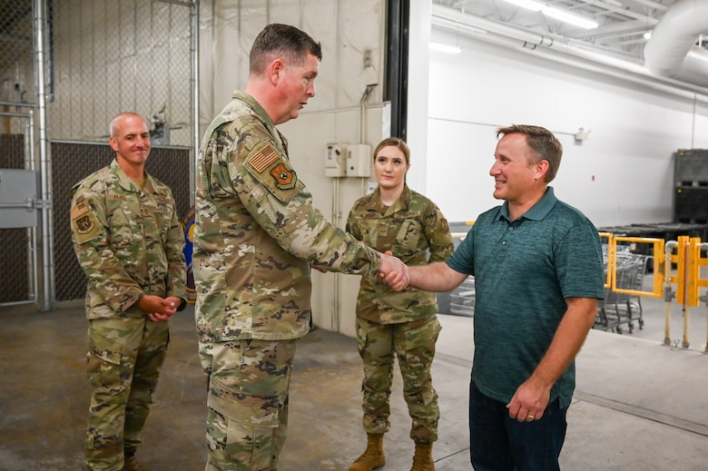 Blaine Haycock and Lt. Gen. Kirkland shake hands while Chief Master Sgt. David Flosi and another Airman look on in the background.