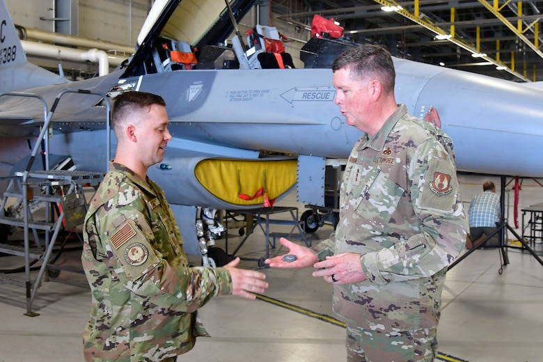 Tech. Sgt. Dominic Dizes holds his hand out to Lt. Gen. Kirkland who is holding a commander's coin in his palm.