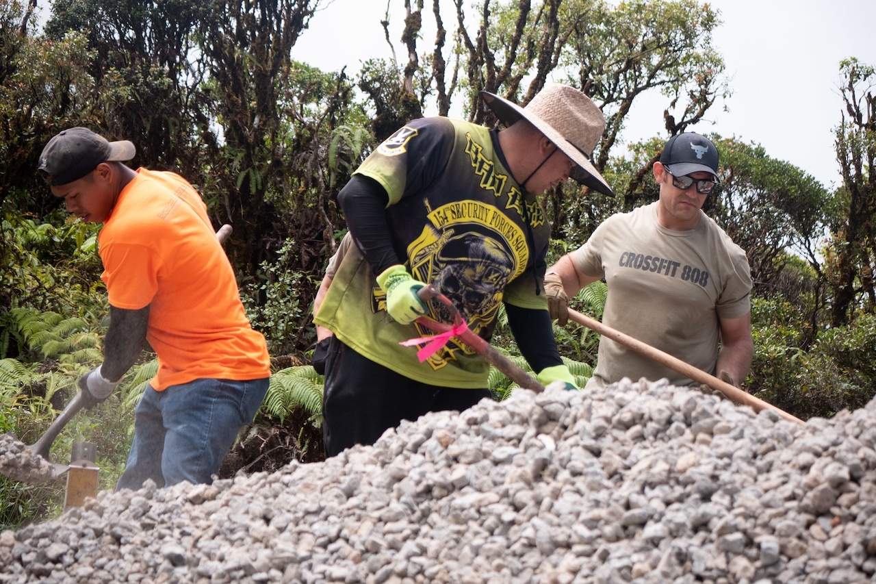 Three airmen shovel gravel.