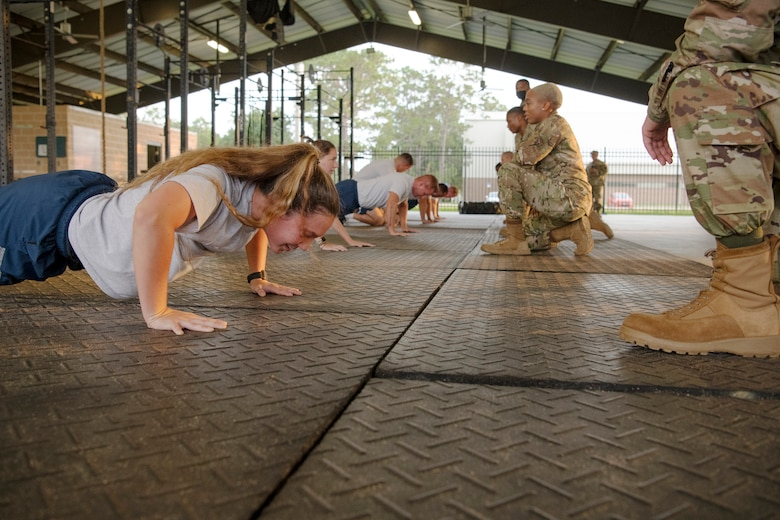 (Front left) Staff Sgt. April Prine, 919th Special Operations Logistics Readiness Squadron Individual Protective Equipment supervisor and members of the 919th Special Operations Wing participate in the Air Force physical fitness test, July 11, 2021. Each Airman are to complete as many push-ups in one minute. After completing the push-ups, the Airmen had the sit-ups requirement, and a 1.5-mile run to complete the AF physical fitness test. (U.S. Air Force photo by Michelle Gigante)