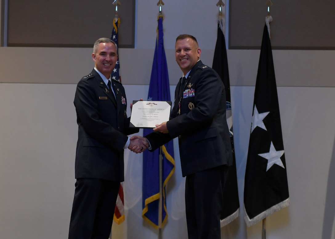 Col. Richard Bourquin, outgoing Space Delta 4 commander, poses with Lt. Gen. Stephen Whiting, Space Operations Command commander, after receiving the Legion of Merit medal during a change of command ceremony at Buckley Space Force Base, Colo., July 15, 2021. Prior to receiving the medal, Whiting reflected on Bourquin's tenure as the first DEL 4 commander. (U.S. Space Force photo by Airman 1st Class Haley N. Blevins)
