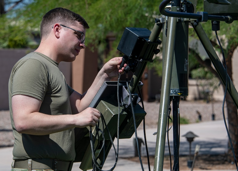A photo of an airmen next to a weather station
