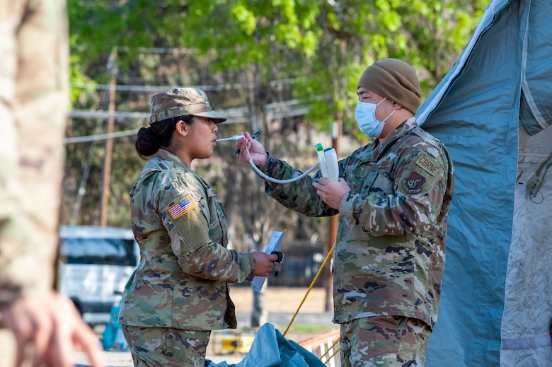 A California Army National Guard soldier with the 95th Civil Support Team has her temperature checked by Tech. Sgt. Thomas Lee, 154th Medical Group, Detachment 1 respiratory therapist as part of medical monitoring procedures during exercise Sentinel Response 2021 in Concord, CA, Apr. 16, 2021.
