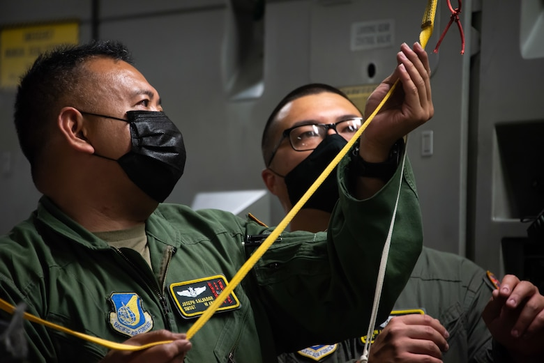 Senior Master Sgt. Joseph Salvador, and Staff Sgt. Justin Lun, 204th Airlift Squadron loadmasters, secure rescue equipment onto a C-17 Globemaster III May 18, 2021, at Moffett Federal Airfield, Calif. Hawaii
