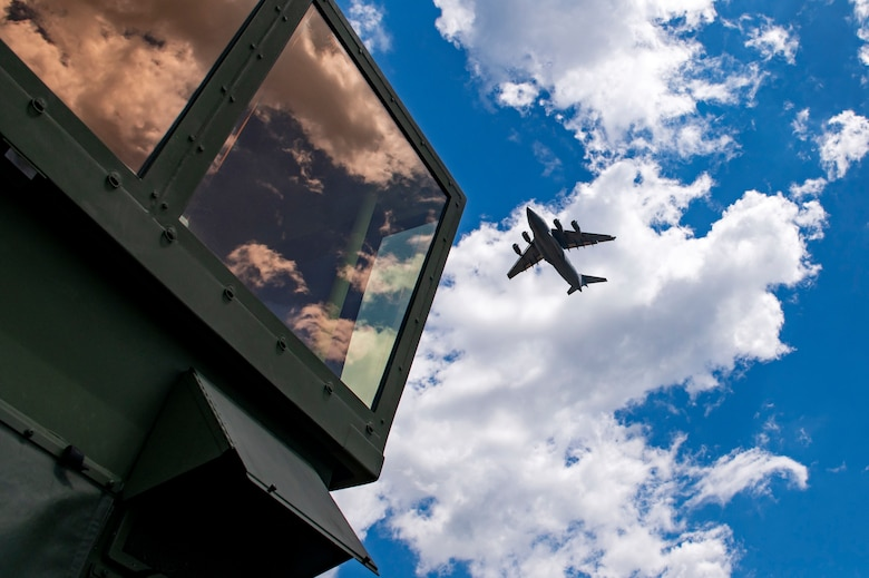 A U.S. Air Force C-17 Globemaster III from the 167th Airlift Wing, West Virginia Air National Guard, performs a low pass over a mobile air traffic control tower at Fort McCoy, Wis., June 14, 2021. PATRIOT 21 is a training exercise designed for civilian emergency management and responders to work with military entities to prepare for disasters.