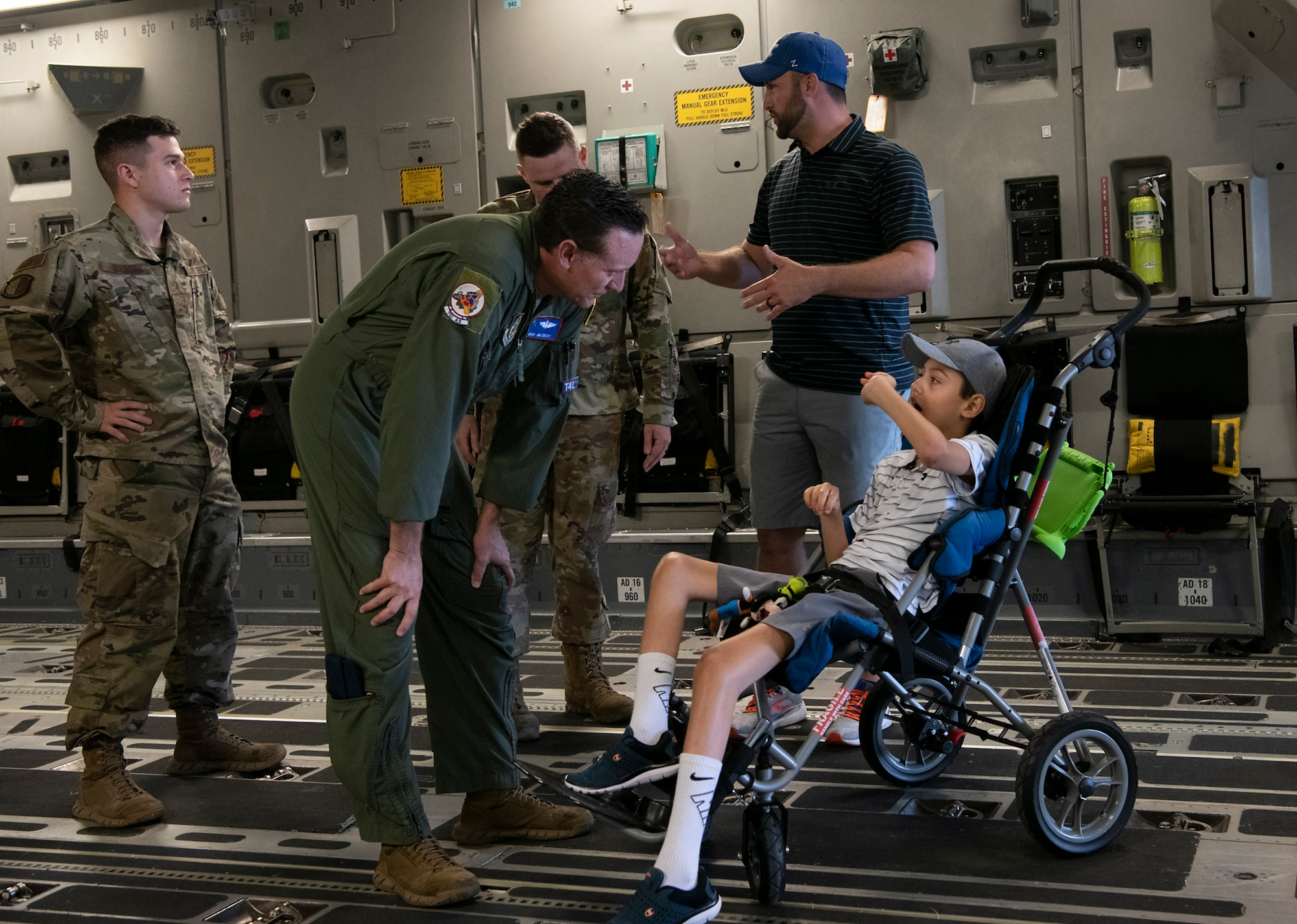 Master Sgt. James Ebert, 701st Airlift Squadron loadmaster, speaks with Braiden Adkins while touring a C-17 Globemaster III at Joint Base Charleston, South Carolina July 14, 2021.