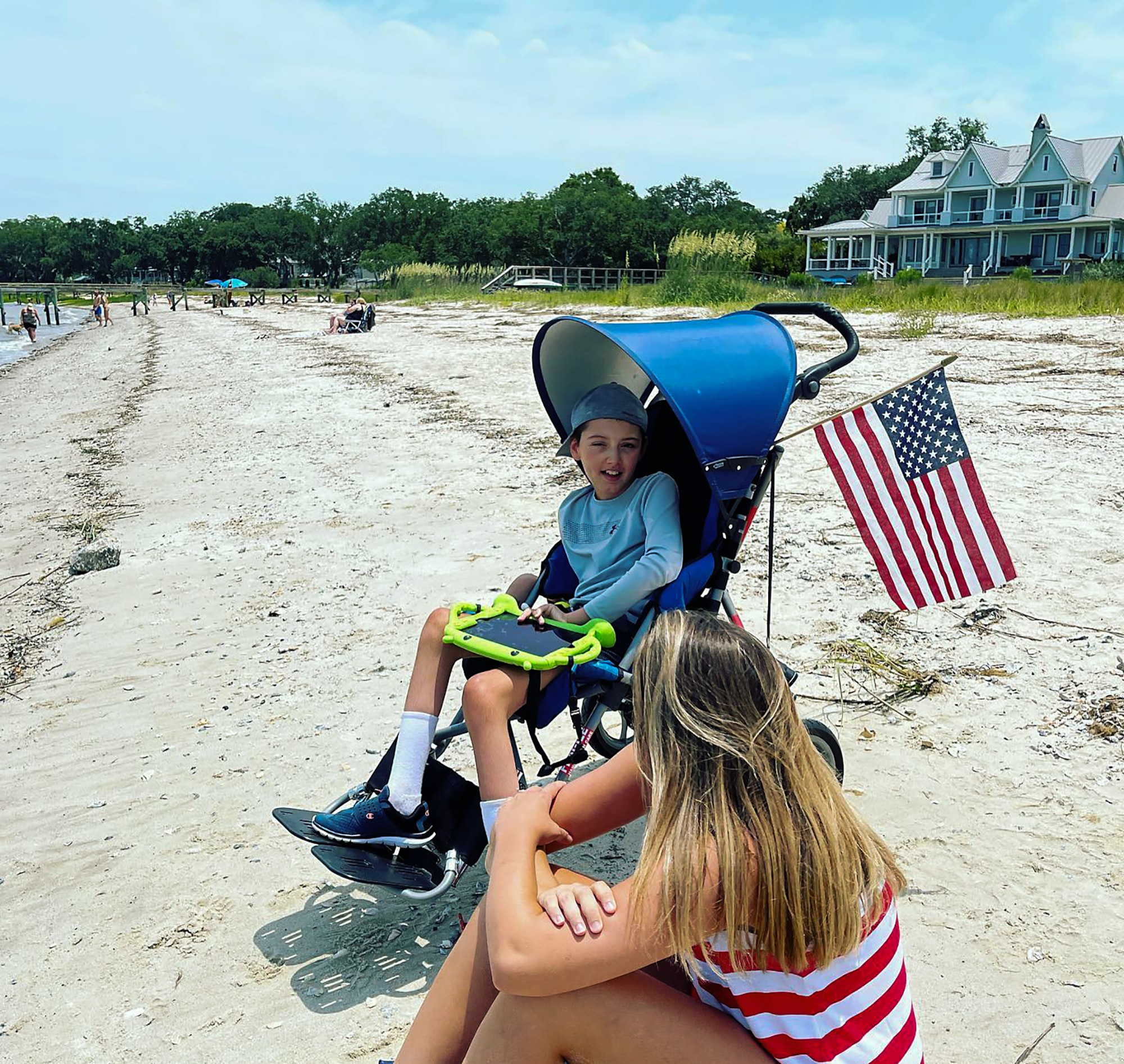 """Airplane fan, Braiden Adkins and his mother Leslie enjoy the annual """"Salute from the Shore"""" celebration in Charleston, South Carolina as a C-17 Globmaster III, flown by the 701st Airlift Squadron,  and other aircraft fly over the South Carolin Coast July 4, 2021"""