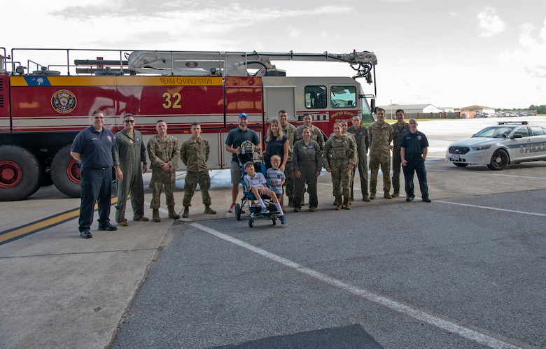 The Adkins family - Matt, Leslie, Braiden and Jace (center) pose for a group photo with aircrew, maintainers, firefighters and security forces at Joint Base Charleston, South Carolina.