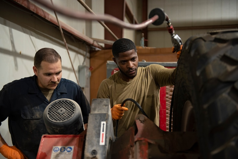 U.S. Air Force Staff Sgt. Douglas Johnson, (left) a vehicle maintainer assigned to the 386th Expeditionary Logistics Readiness Squadron, assists U.S. Air Force Senior Airman Dalfred Sonnier (right) a vehicle maintainer assigned to the 386th Expeditionary Logistics Readiness Squadron, fill a tire with air at Ali Al Salem Air Base, Kuwait, July 8, 2021.