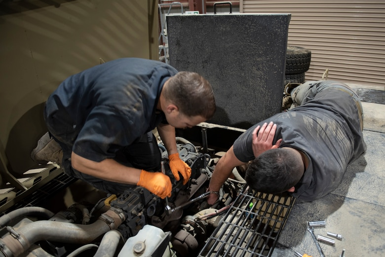 U.S. Air Force Staff Sgt. Douglas Johnson, (left) a vehicle maintainer assigned to the 386th Expeditionary Logistics Readiness Squadron, helps U.S. Air Force Staff Sgt. Brice Thompson, (right) a vehicle maintainer assigned to the 386th Expeditionary Logistics Readiness Squadron, change a starter in a MV-2 toe tractor at Ali Al Salem Air Base, Kuwait, July 8, 2021.