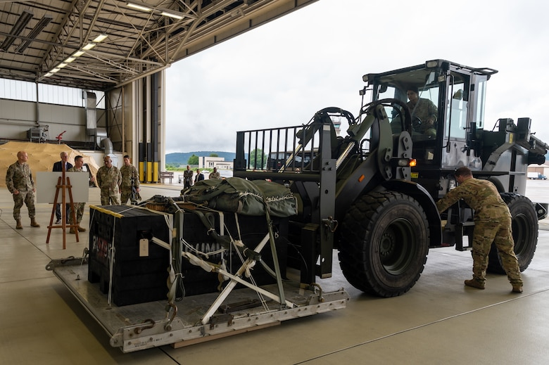 CSAF and other leadership watching Airmen operate a heavy duty forklift.