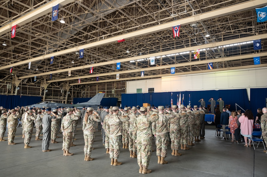 A group of people in uniform salute a stage and three uniformed people.
