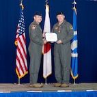Man in uniform hands a certificate to another.