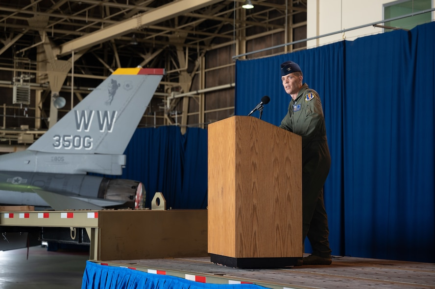 A man in uniform speaks from a podium in front of a fighter jet.